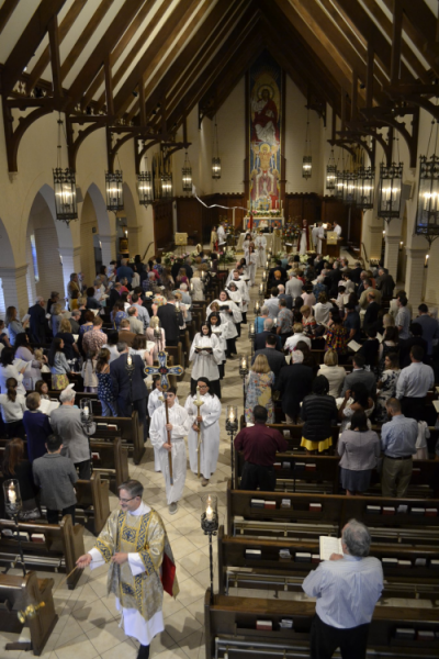 A procession walks down the main aisle of the church.